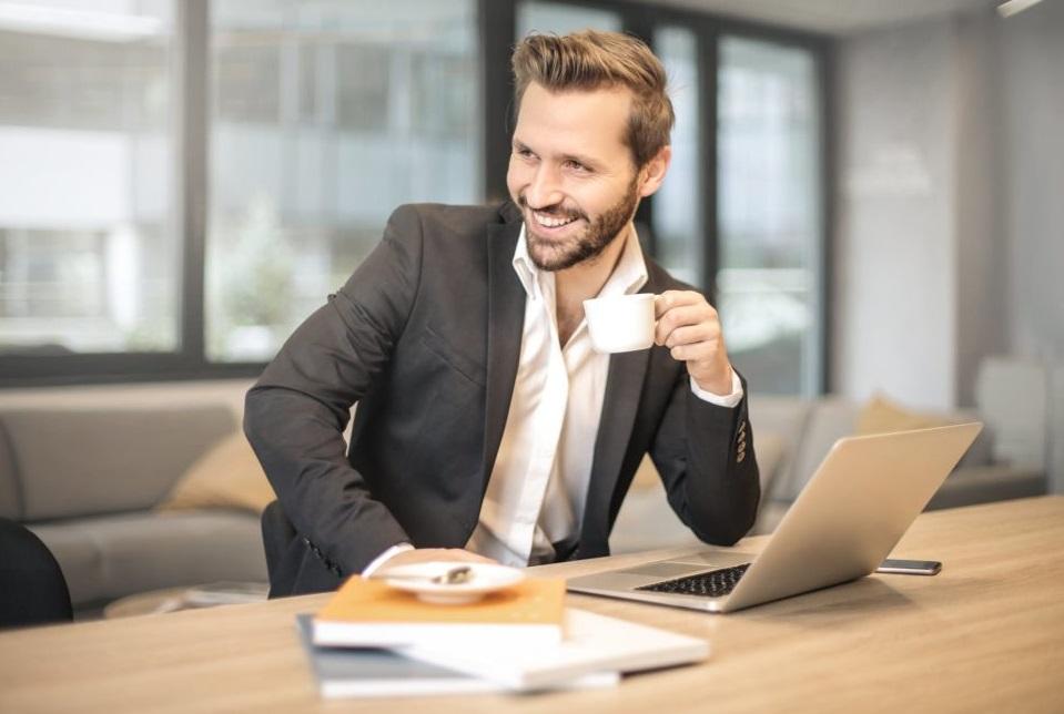 Homme buvant un café devant son ordinateur