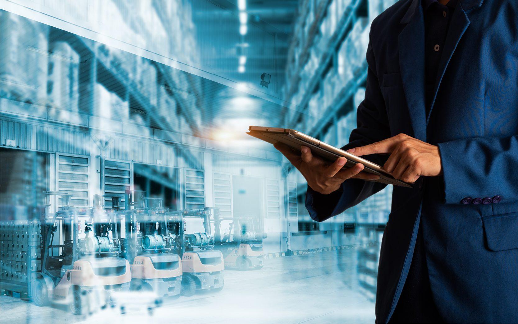 Un homme avec un iPad et une usine au dernier plan