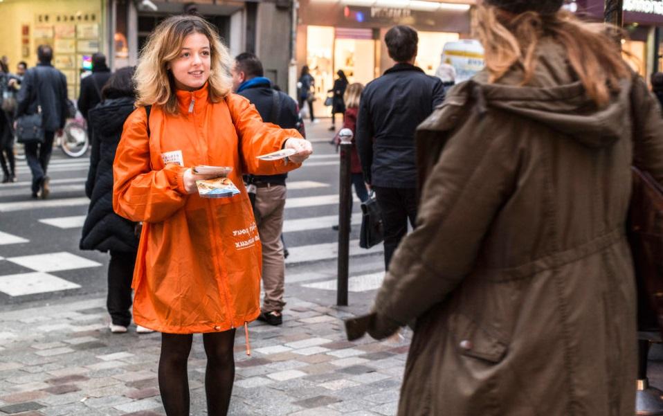 femme distribution flyers rue piétons route