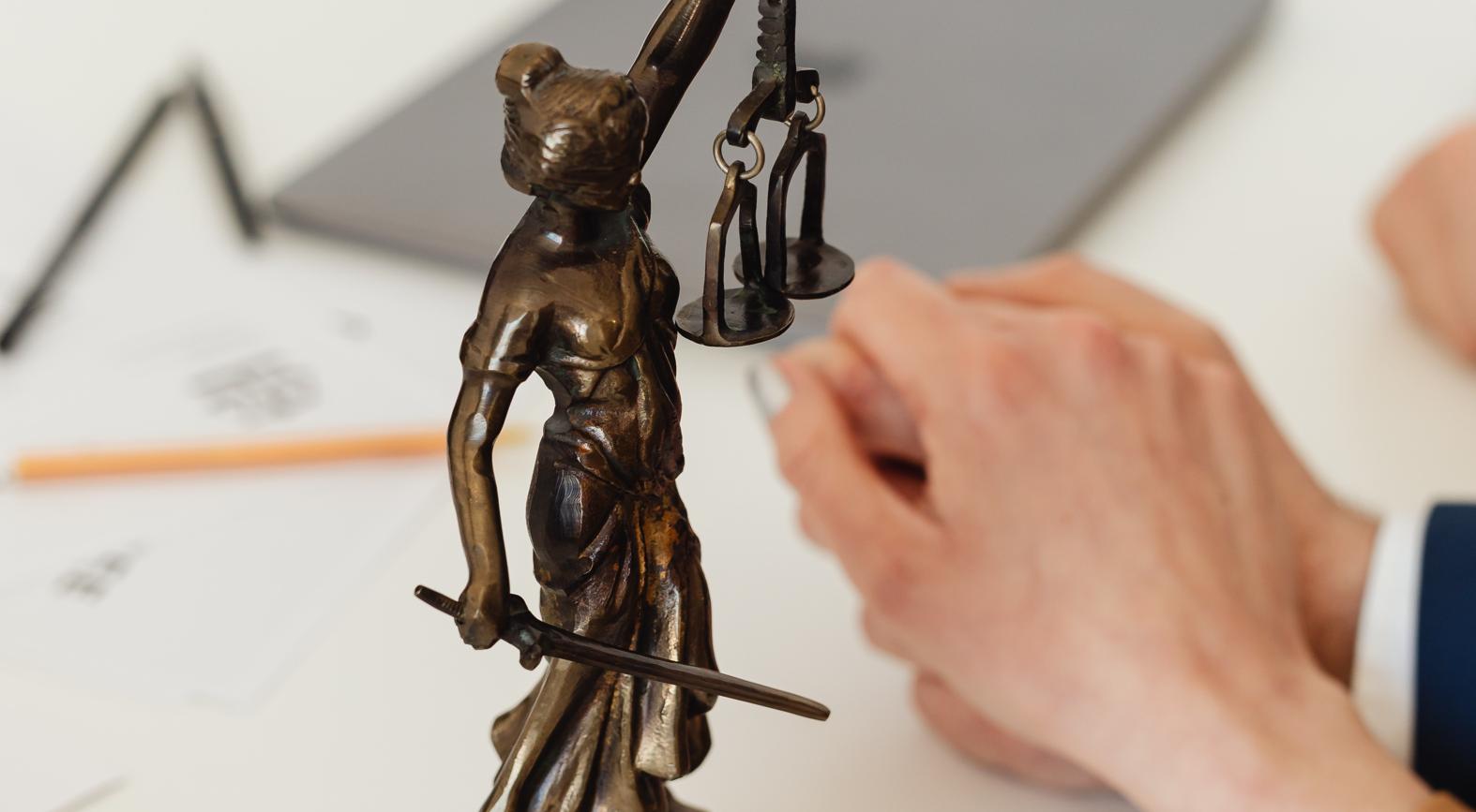 statue de justice devant mains liées